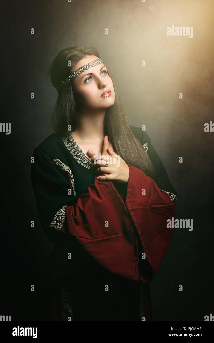 Bela mulher medieval orando no soft luz sagrada . Histórico e religião Imagens de Stock
