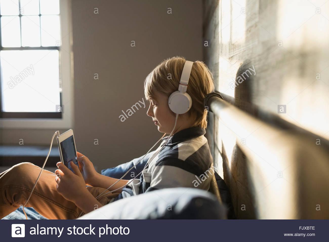 Rapaz com fones de ouvido usando tablet digital Imagens de Stock