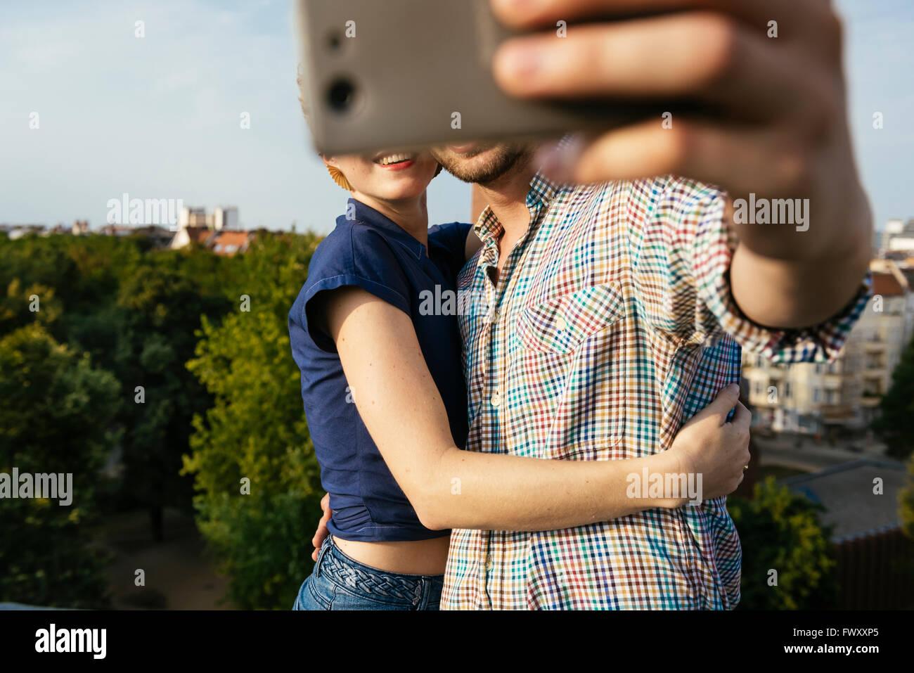 Alemanha, Berlim, jovem casal abraçando e tendo selfie com telefone smart Imagens de Stock