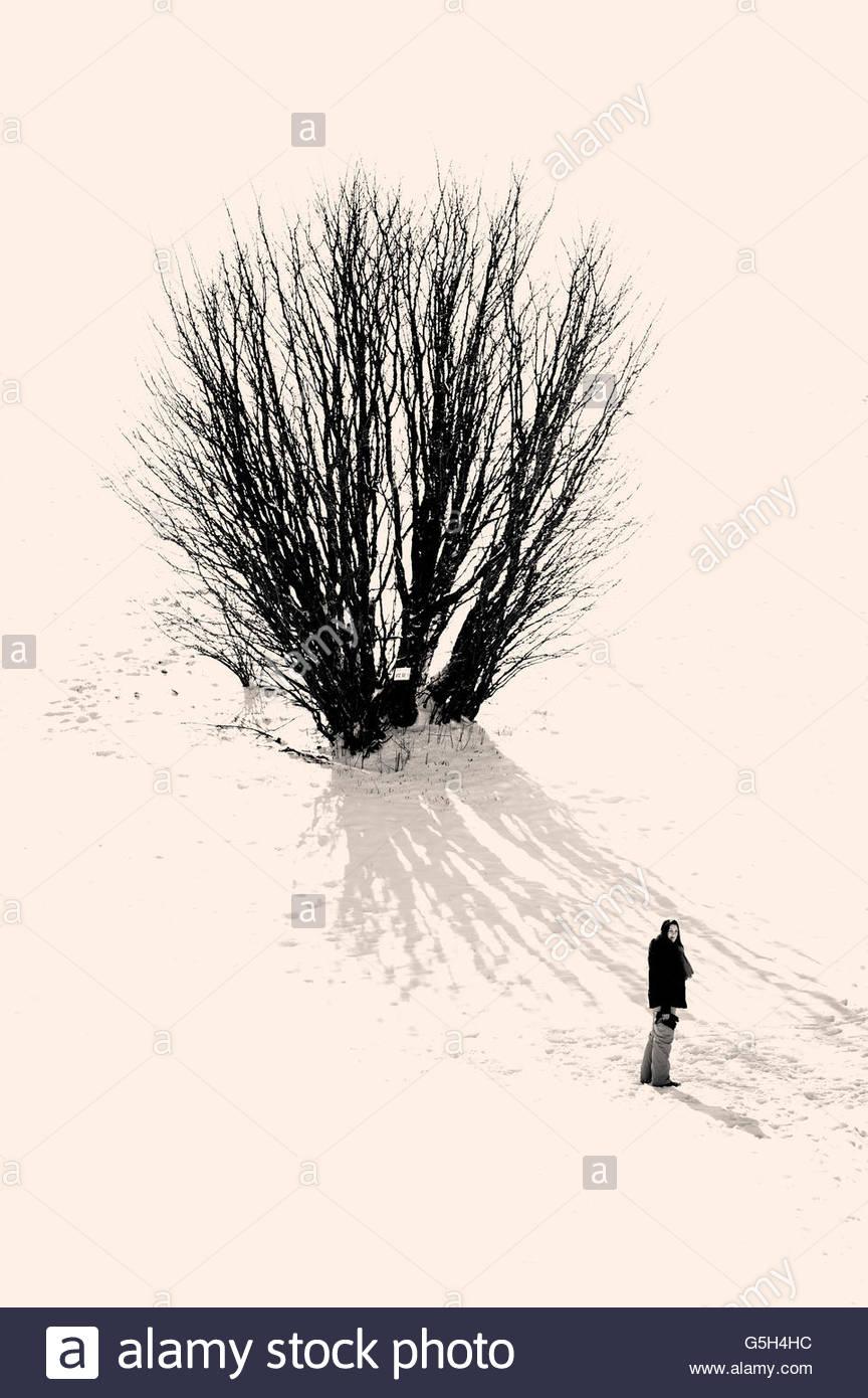 Garota em um está harmoniosamente enquadrado na paisagem de neve Imagens de Stock
