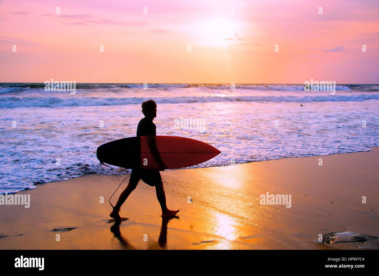 Surfista com prancha de caminhar sobre a areia da praia ao pôr-do-sol. Ilha de Bali, Indonésia Imagens de Stock