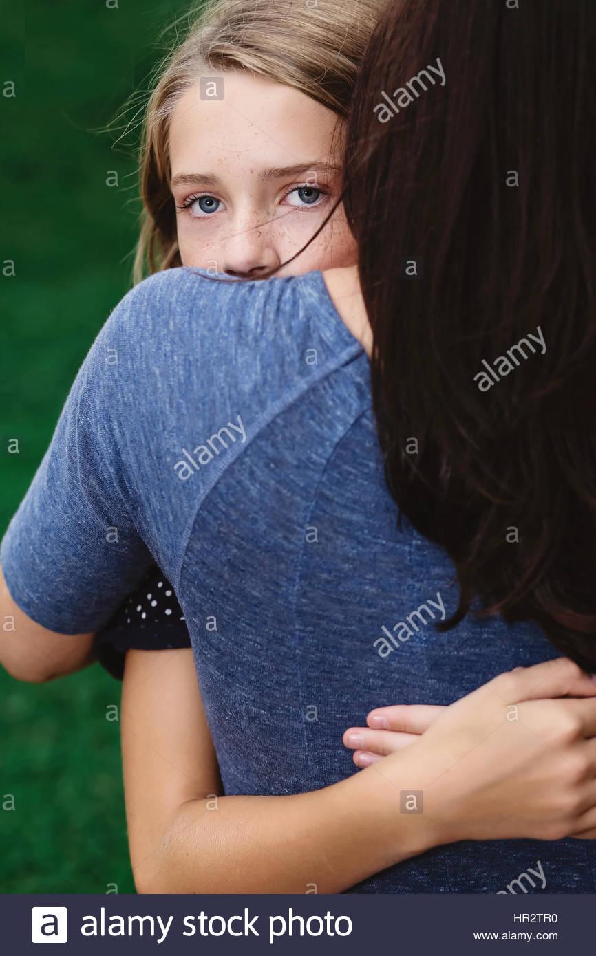Filha abraçar a mãe e a olhar por cima do seu ombro Imagens de Stock