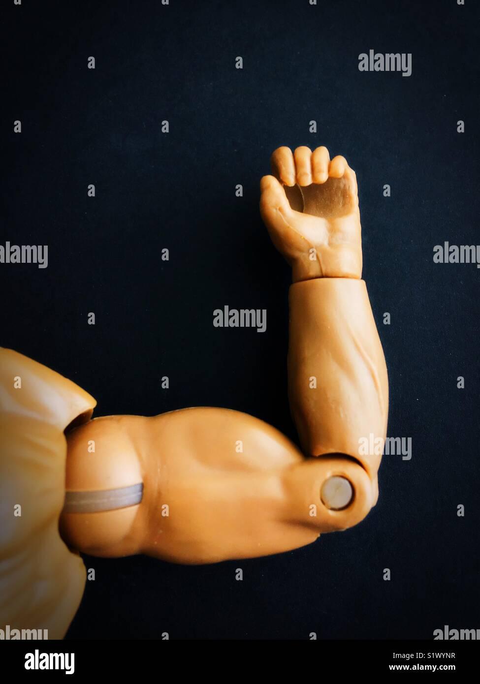 Close up de uma boneca de plástico macho flexão do braço do músculo. Imagens de Stock