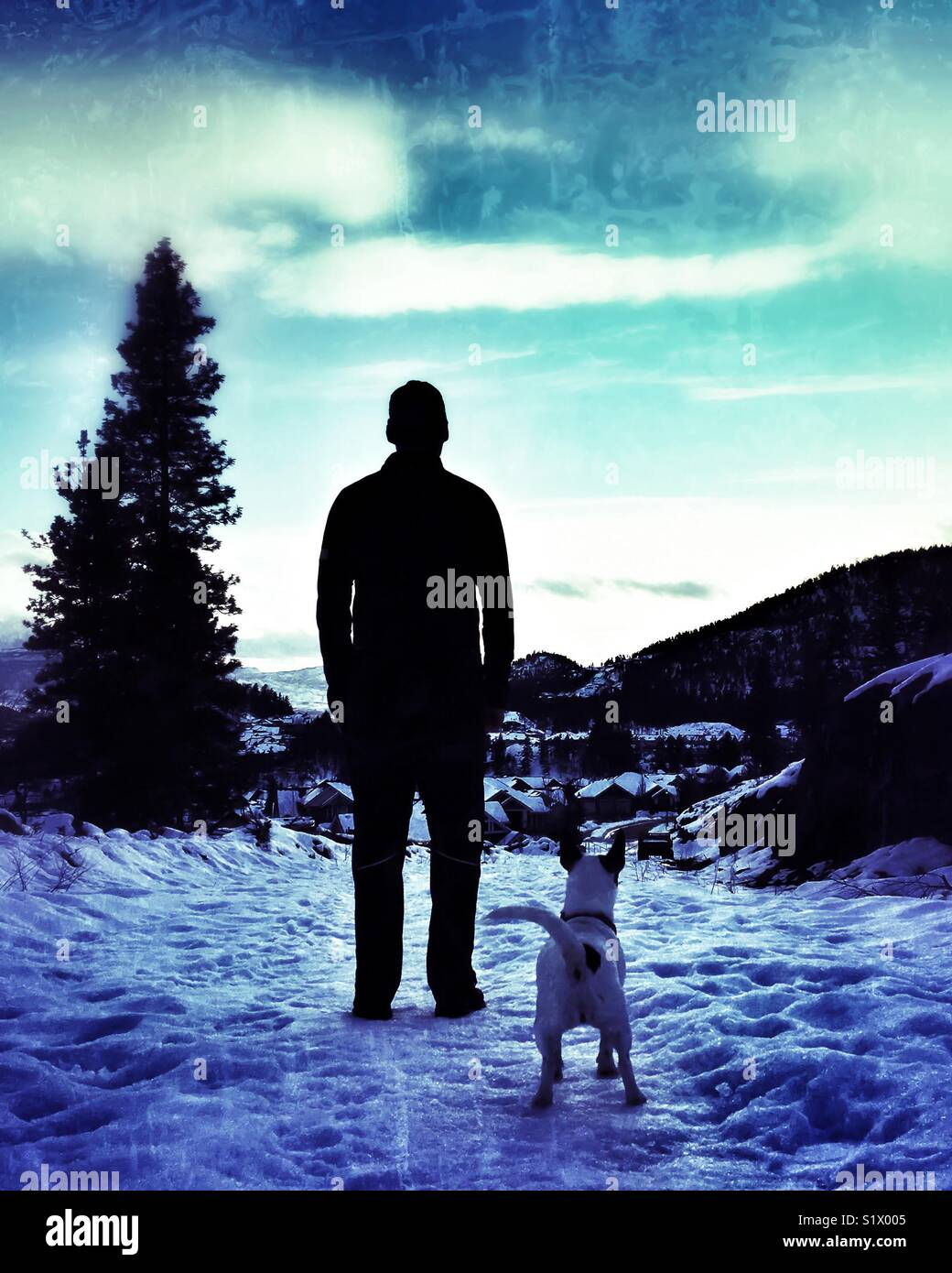 Silhueta de um homem em pé na neve com o seu cão. Imagens de Stock