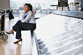 african-woman-waiting-at-airport-baggage