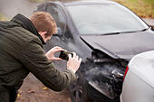 man-taking-photo-of-car-accident-on-mobi
