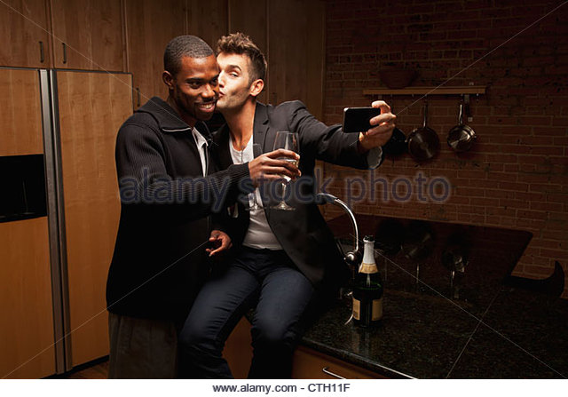 Gay couple drinking wine in kitchen and taking self-portraits - Stock Image
