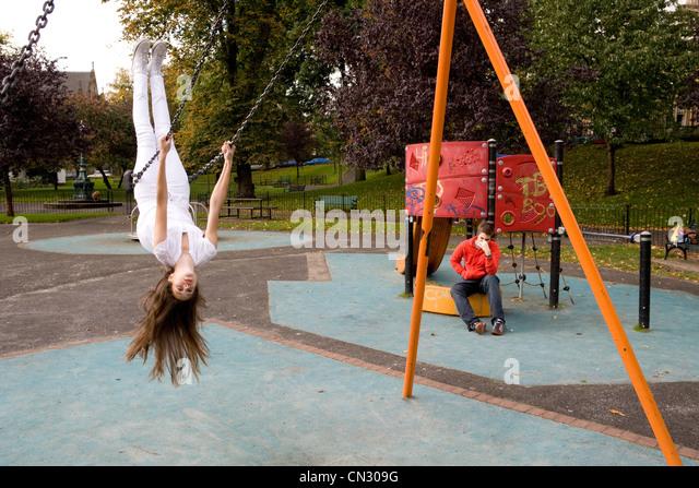 Teenage girl on swing in playground, upside down - Stock Image