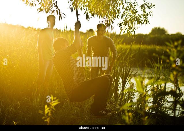 Caucasian men playing on rope swing at lake - Stock Image