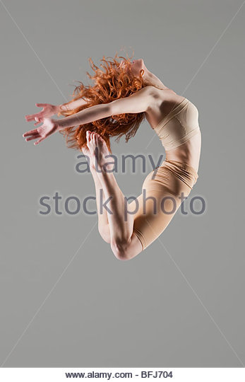 Dancer jumps with arms and legs bending nackwards - Stock Image