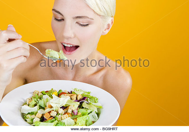 A Young Woman Eating Salad - Stock Image