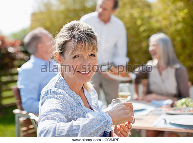Portrait of smiling senior woman enjoying lunch with friends at sunny table - Stock Image
