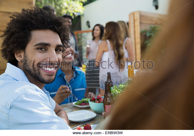 Portrait smiling man eating lunch at patio table - Stock Image