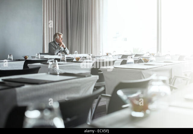 Mature businessman sitting in office restaurant with hands clasped - Stock Image