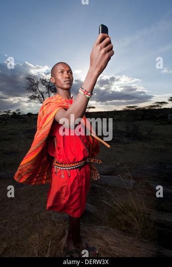 Maasai holding up mobile phone to get better reception, Mara Region, Kenya. - Stock Image