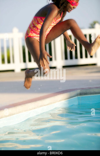 African American girl jumping into a swimming pool. - Stock Image