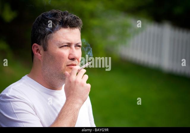 man-smoking-a-cigarette-outside-bayg9r.j