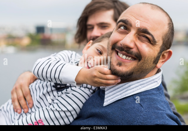 Happy son playing with gay man's beards outdoors - Stock Image