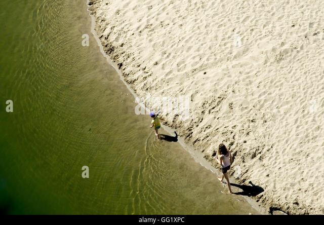 mother-and-son-walking-along-the-shoreli