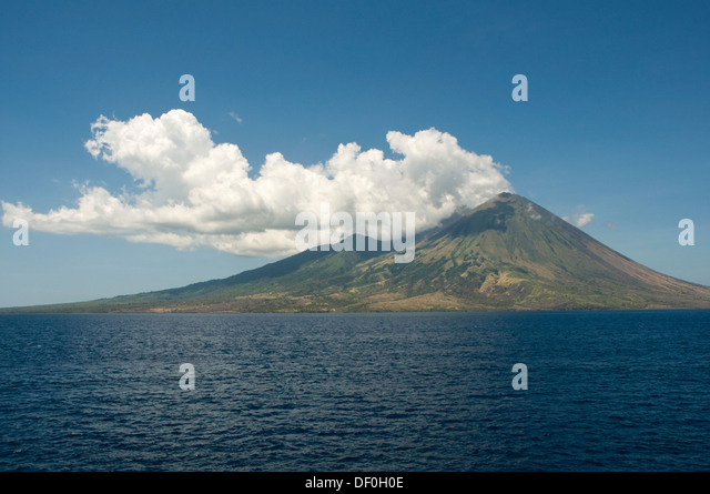 INDONESIA, Sumbawa Island, volcano with cloud and blue sky pictured from the sea - Stock Image