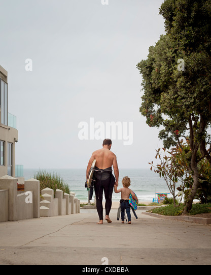 Caucasian father and son in wetsuits walking toward the ocean - Stock Image