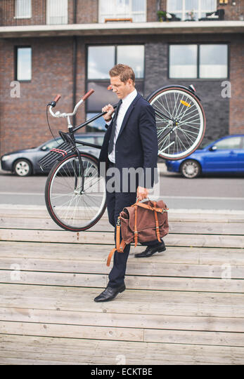Full length of businessman carrying bicycle while walking on steps - Stock Image