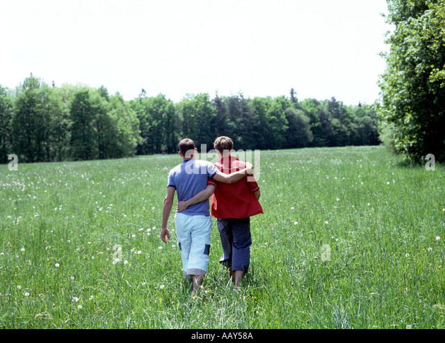 a gay couple walking in the grass view from behind - Stock Image