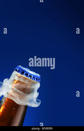 A lid takes off from the bottle of beer - Stock Image
