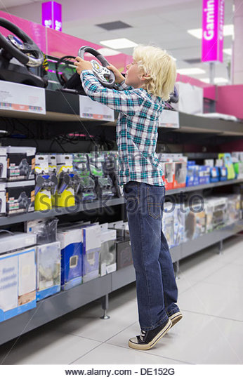Boy reaching up for video game steering wheel in electronics store - Stock Image