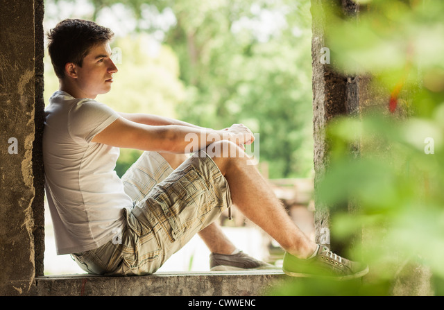 Man sitting in windowsill - Stock Image