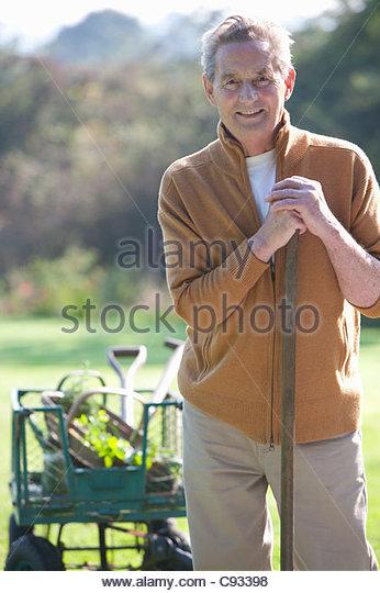 Portrait of smiling senior man with gardening tools - Stock Image