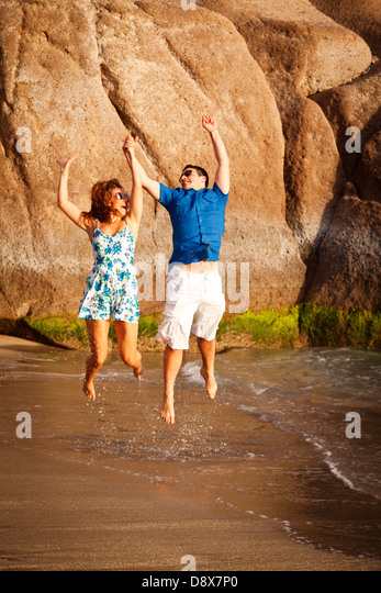 young-couple-on-the-beach-jumping-for-jo
