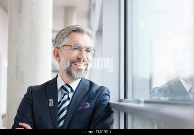 Confident businessman looking out of window - Stock Image
