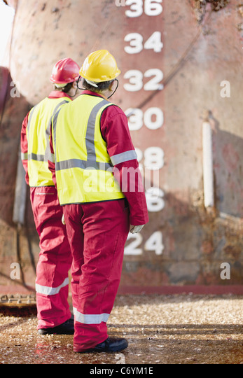 Workers standing on oil rig - Stock Image