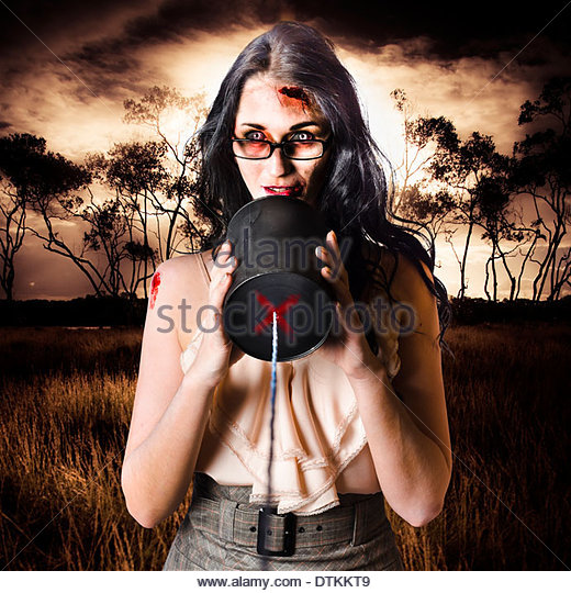 Concept photograph of a female model in devil makeup making a halloween announcement through a tin can phone. Dark - Stock Image