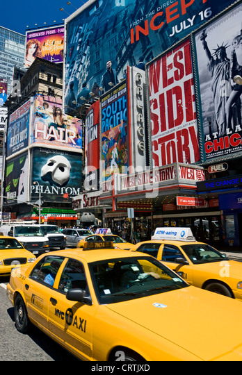 Yellow taxis in Times Square, New York City during daytime. - Stock Image