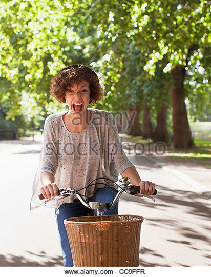 Exuberant woman with mouth open riding bicycle in park - Stock Image