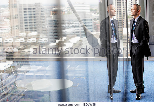 Businessman Standing Beside a Giant Office Window - Stock Image