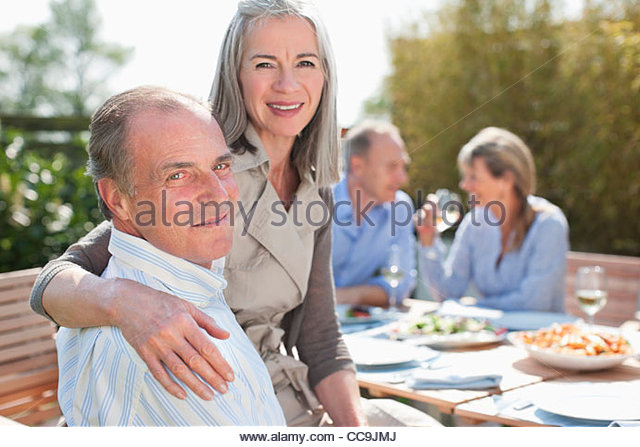 Portrait of senior couple enjoying lunch at table in sunny garden with friends - Stock Image