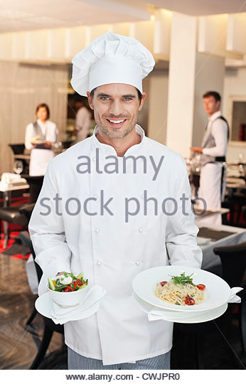 Portrait of smiling chef holding salad and entree - Stock Image
