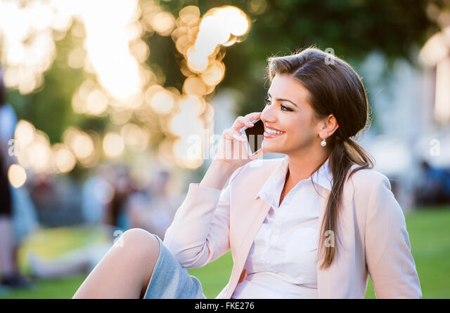 http://c7.alamy.com/zooms/2e79ccb9eeae42e096e1b776b403070c/businesswoman-sitting-in-park-making-a-phone-call-sunny-day-fke276.jpg