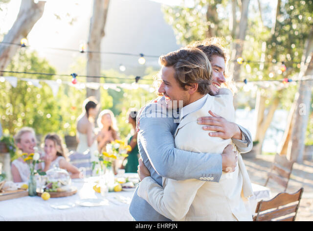 Bridegroom and best man embracing during wedding reception in domestic garden - Stock Image