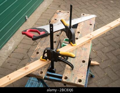 DIY using Workzone Quick Ratcheting Bar Clamps to hold a wooden workpiece onto a B&D Workmate workbench while sawing. - Stock Image