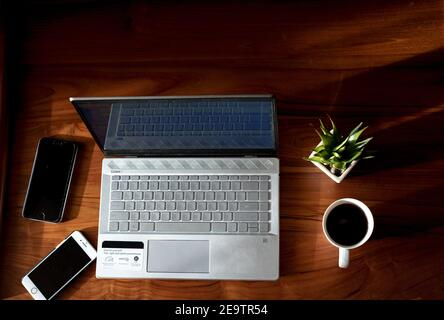 IT professional women working from home with Laptop and Phones with a hot cup of coffee beside and a green plant - Stock Image