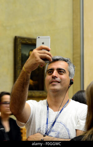 A man gets a selfie with the Mona Lisa. - Stock Image