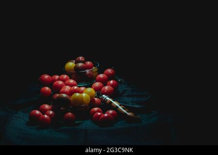 cherry tomatoes, on black tablecloth, next to wooden razor, and black background illuminated from above, with bright colors, concept of healthy vegeta - Stock Image