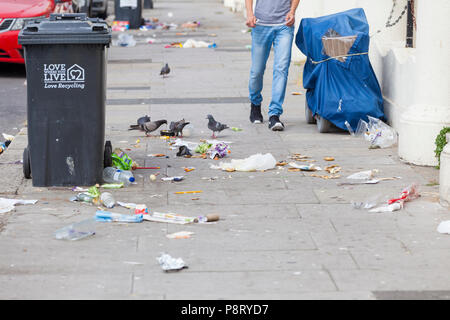 Litter strewn street with pigeons picking at rubbish lying on the pavement in hastings, east sussex, uk - Stock Image