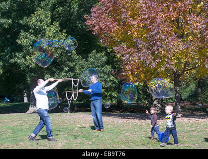 Men making monster soap bubbles with young children watching in Prospect Park Brooklyn, NYC, USA - Stock Image