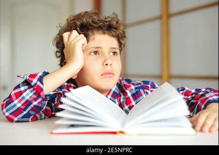 Little boy with curly hair doing homework and looking thoughtfully and dreamily - Stock Image