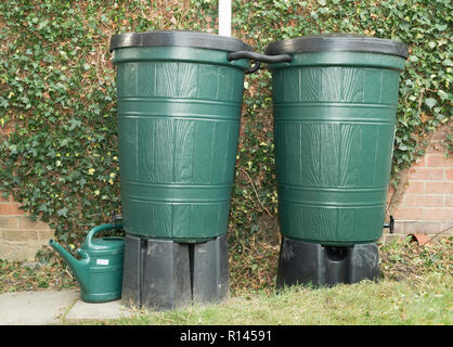 Two connected water butts in a domestic garden, England, UK - Stock Image